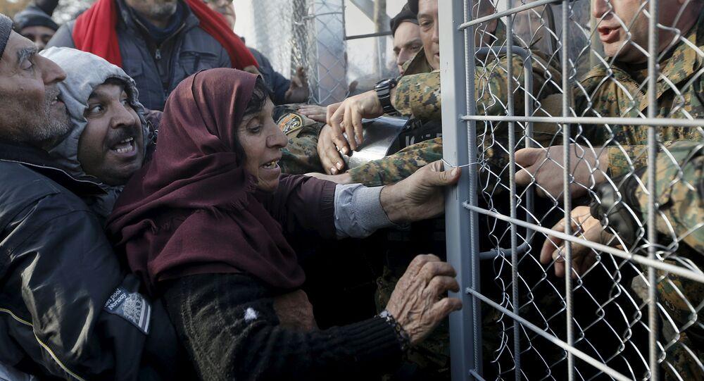 Syrian refugees struggle to enter Macedonia through a narrow border crossing as Macedonian policemen try to shut a metal gate near to the Greek village of Idomeni December 4, 2015