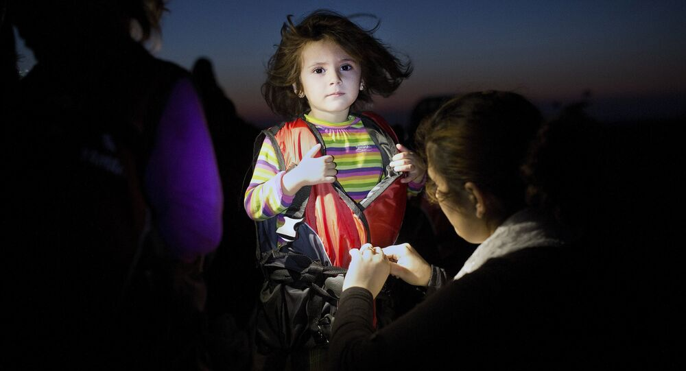 A child gets assistance to remove her life jacket upon her arrival on an inflatable boat carrying migrants on the Greek island of Kos after crossing a part of the Aegean Sea between Turkey and Greece on August 13, 2015.