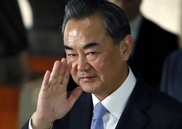 Chinese Foreign Minster Wang Yi waves to the media as he leaves the Department of Foreign Affairs following his talks with Philippine Foreign Secretary Albert Del Rosario Tuesday, Nov. 10, 2015 at suburban Pasay city, south of Manila, Philippines