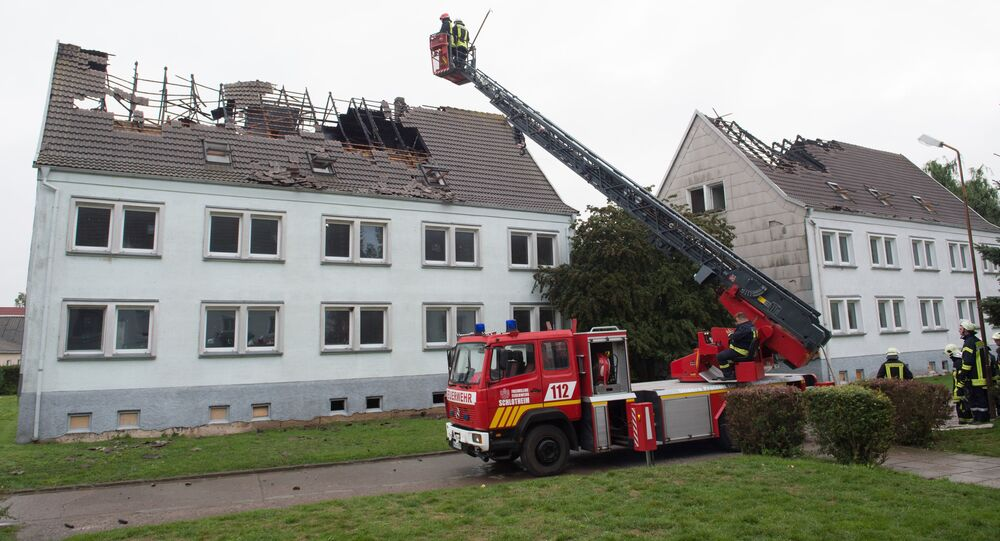 Firefighters look at a house that was meant to shelter migrants in Ebeleben, eastern Germany, Monday Sept. 7, 2015