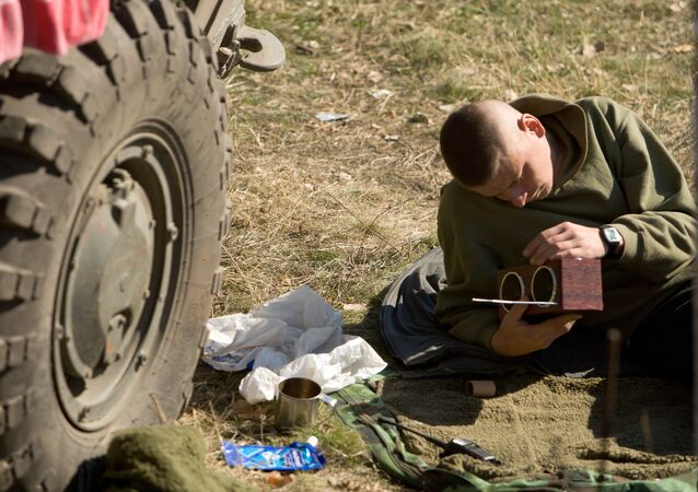A Ukrainian serviceman listens to the radio as he rests in a base camp near the town of Debaltsevo in the Donetsk region. File photo.
