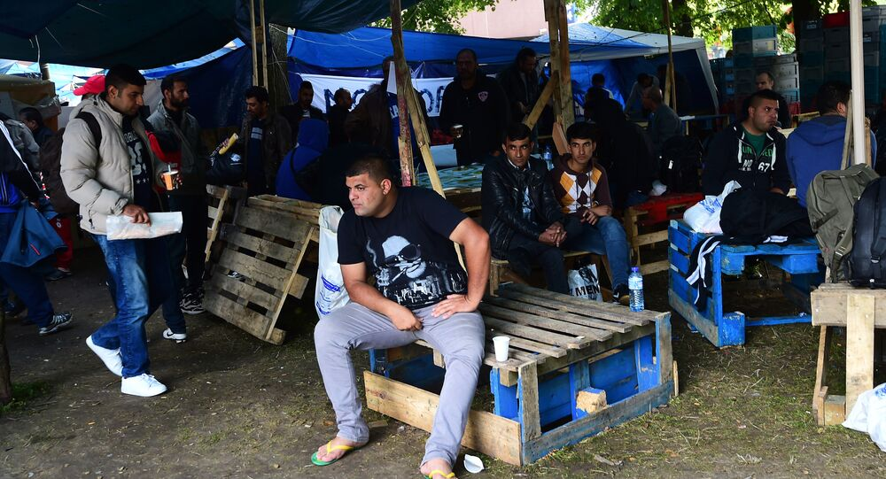 Migrants wait in a makeshift tent camp in a park in Brussels on September 9, 2015, as they wait to have their asylum claims processed