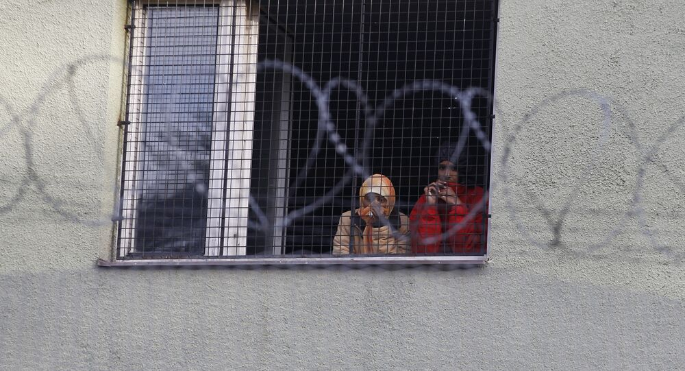 Migrants look out of a window at the Bela-Jezova refugee facility in Bela pod Bezdezem, Czech Republic, Thursday, Nov. 5, 2015