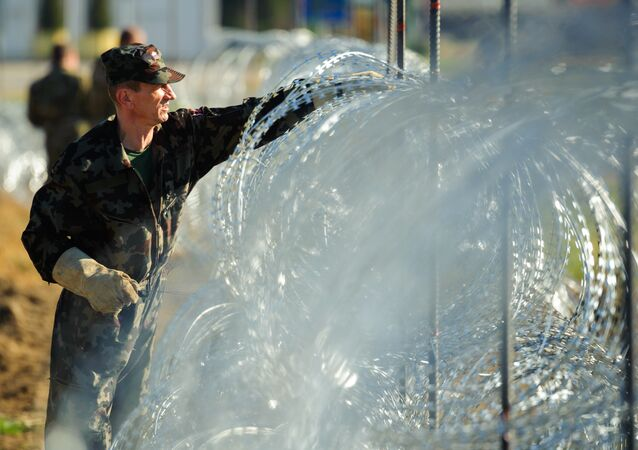 Slovenian soldiers build a razor wire fence on the Slovenian-Croatian border in Gibina, northeastern Slovenia, on November 11, 2015