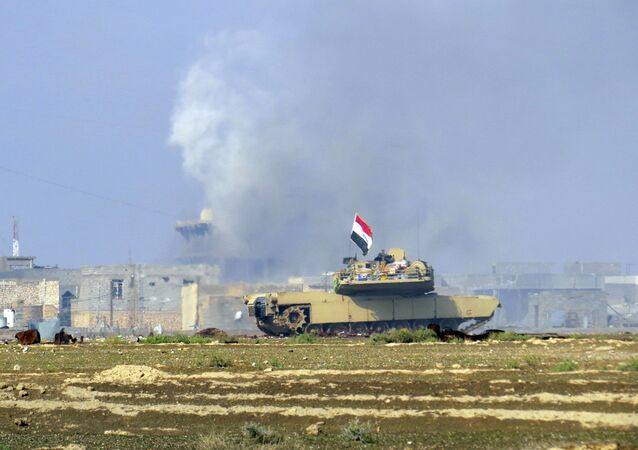A national flag waves on an Iraqi Army Abrams tank as Iraqi forces supported by U.S.-led coalition airstrikes advance their position during clashes with Islamic State group in the western suburbs of Ramadi, the capital of Iraq's Anbar province, 70 miles (115 kilometers) west of Baghdad, Iraq, Saturday, Nov. 21, 2015