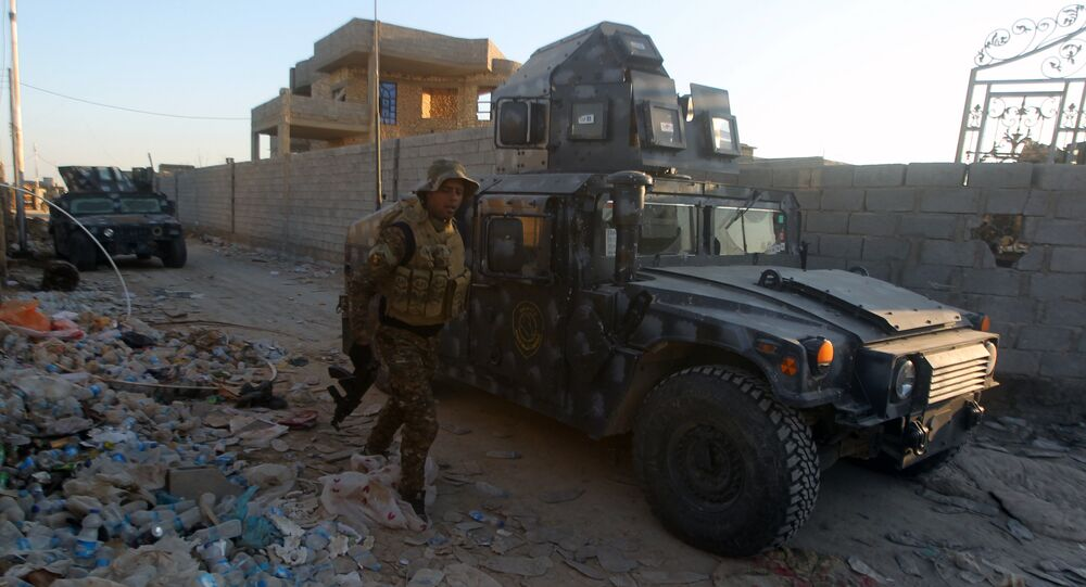 Iraqi troops and allied paramilitaries advance on December 6, 2015 down a street in Husayba, an Iraqi rural town in the Euphrates Valley seven kilometres (4.5 miles) east of Ramadi, where government forces have been closing on Islamic State (IS) group militants who seized the Anbar province's capital in May after a three-day blitz involving dozens of huge truck bombs