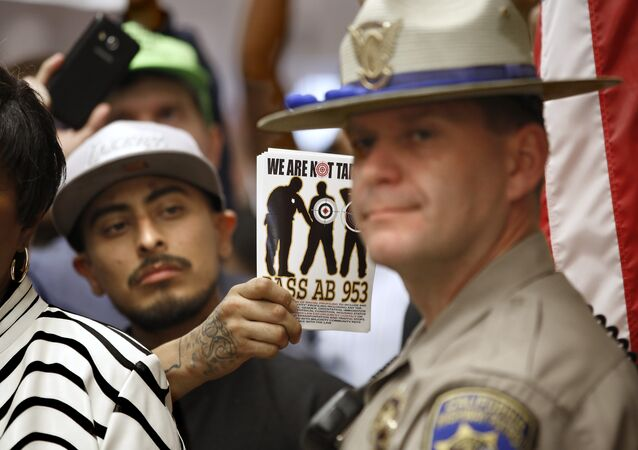 California Highway Patrol Officer J. Nelson stands outside the office of Gov. Jerry Brown as protestors shouting black lives matter block the hallway demanding passage of AB953, Wednesday, Sept. 2, 2015, in Sacramento,Calif.