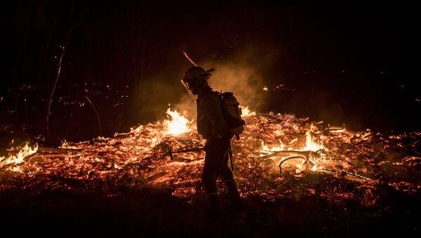 A firefighters tries to extinguish flames - Sputnik International