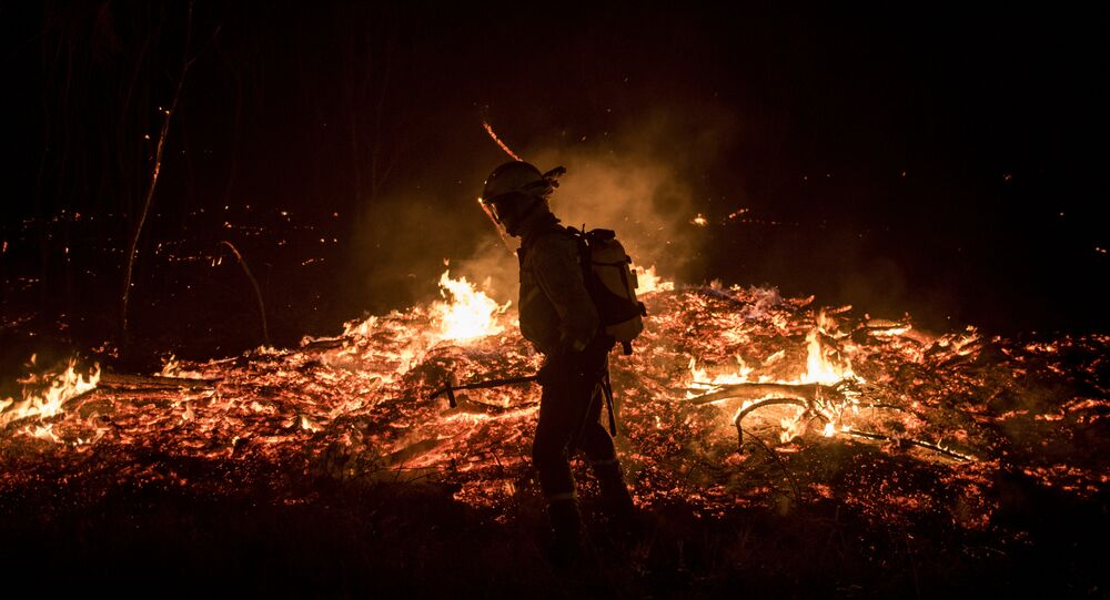 A firefighters tries to extinguish flames