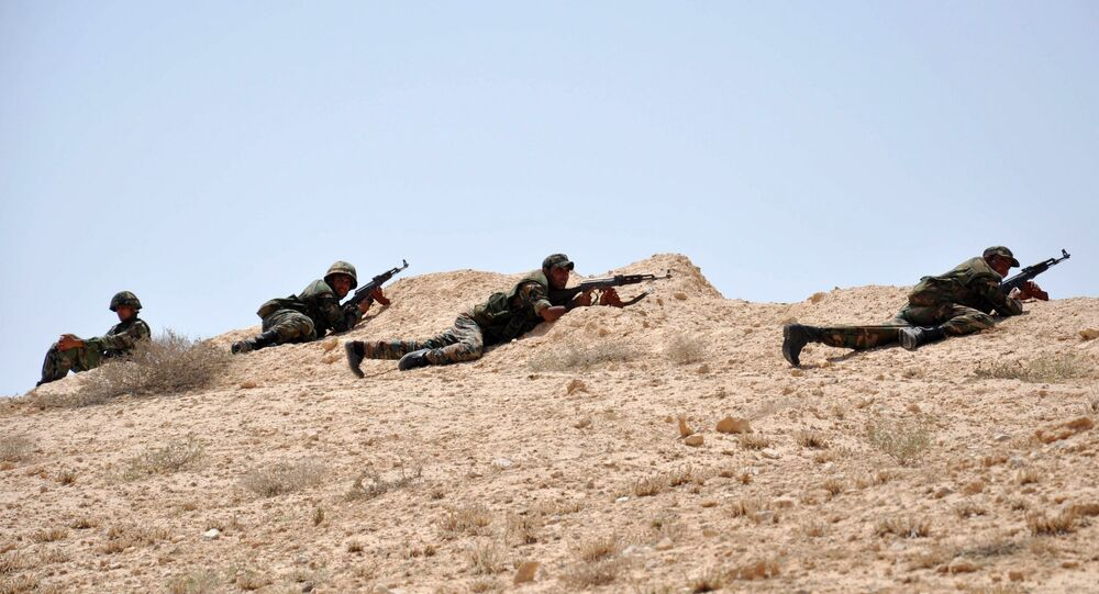Syrian soldiers get in position during clashes with Daesh jihadists in northeastern Palmyra