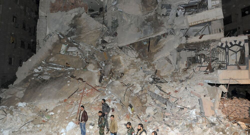 Members of Syrian security services and soldiers stand in front of a damaged building that was hit by an Israeli strike, killing a Lebanese militant leader Samir Qantar, in the Damascus district of Jaramana, Syria in this handout picture provided by SANA on December 20, 2015