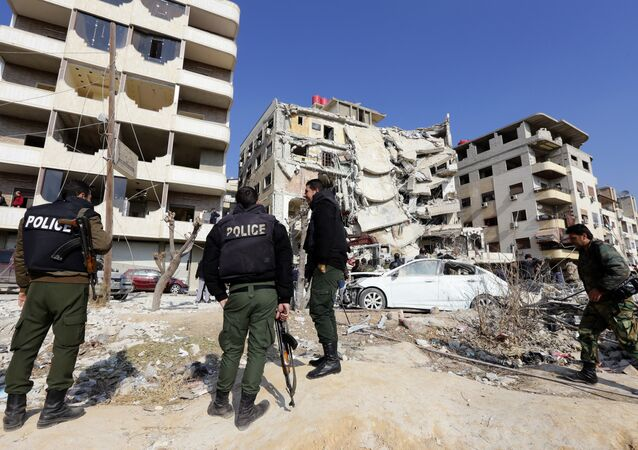 A general view shows Syrian police standing guard at the site of a reported Israeli air raid that killed a senior figure in the Lebanese Shiite militant group Hezbollah, Samir Kantar, in Jaramana, southeast of the Syrian capital Damascus