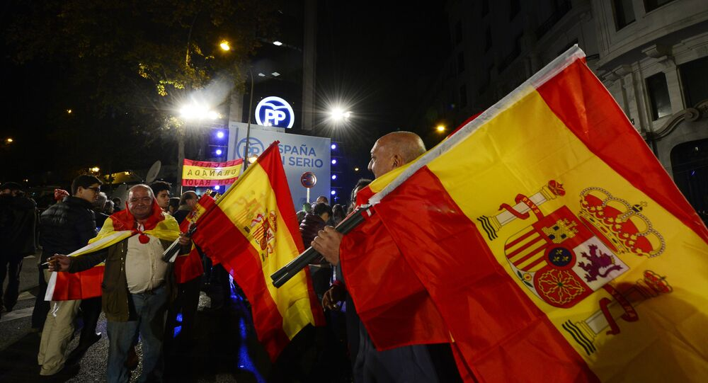 Popular Party (PP) supporters wave Spanish flags in front of the party's headquarters after the partial results of Spain's general elections in Madrid on December 20, 2015.