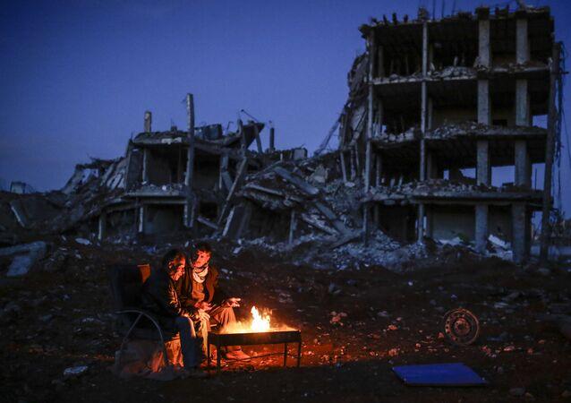 Kurdish men sit near bonfire near a destroyed building, in the Syrian Kurdish town of Kobane, also known as Ain al-Arab
