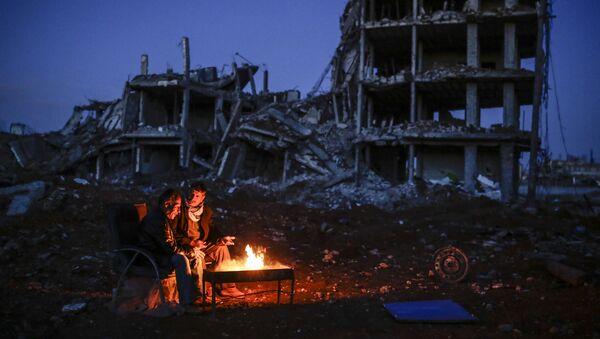 Kurdish men sit near bonfire near a destroyed building, in the Syrian Kurdish town of Kobane, also known as Ain al-Arab - Sputnik International