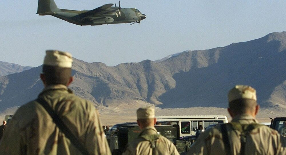 American soldiers watch a Hercules C-130 plane take off at the Bargam airbase north of Kabul