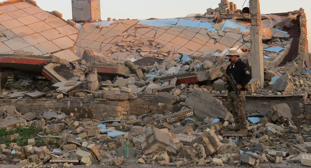 A member of the Iraqi security forces stands in the rubble of destroyed buildings in the rural Husayba al-Sharkiya area, east of Anbar province's capital Ramadi, as they undertake military operations to attack Islamic State (IS) group positions on December 20, 2015.