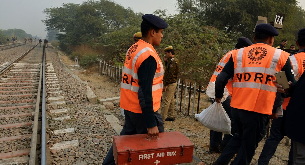 Members of the National Disaster Response Force (NDRF) direct operations near the crash site of a chartered army plane close to the main airport in New Delhi on December 22, 2015