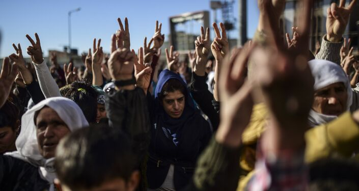 Members of the Kurdish community flash the V for victiry sign during a demonstration in Sirnak