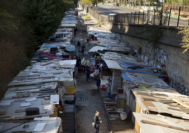 People walk between makeshift shelters of the Roma camp at the boulevard Ney in Paris