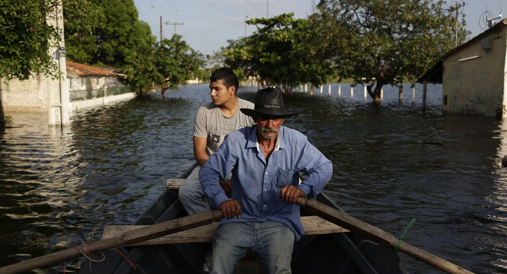 Victor Ferreira, who is displaced by flooding, rows his boat through the streets of his Jukyty neighborhood in Asuncion, Paraguay, Wednesday, Dec. 23, 2015.