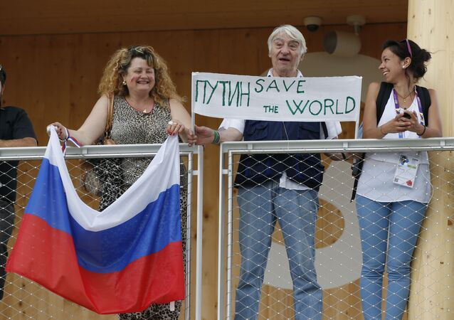 Visitors hold a banner and a Russian flag as Russian President Vladimir Putin arrives for a visit at the Russian pavilion at the 2015 Expo in Rho, near Milan, Italy, Wednesday, June 10, 2015