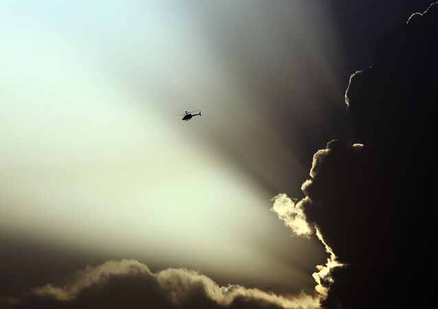 A US helicopter flies during clashes between Taliban fighters and Afghan government forces in Kabul, Afghanistan.