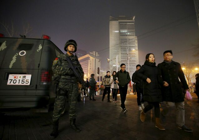 An armed policeman from the Snow Leopard Commando Unit stands guard next to a police van at the Sanlitun area, a fashionable location for shopping and dining, on Christmas Eve in Beijing, China, December 24, 2015.