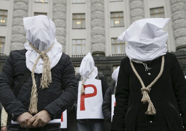 Activists with bags on their heads and ropes around their necks demand an increase in state funding for the treatment of seriously ill people in front of the government building in Kiev, Ukraine, December 23, 2015