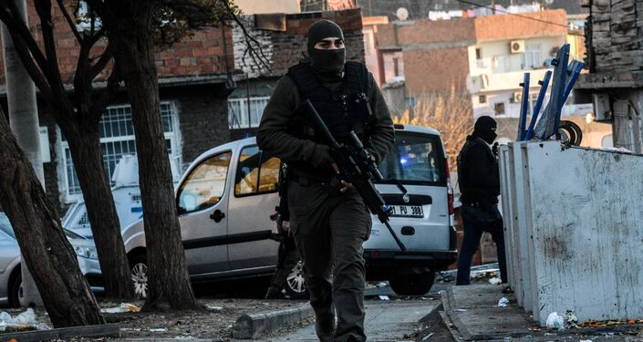 Turkish masked plain clothes police officer patrols a street during a clash between Kurdish activists and Turkish police in the historical Sur district on December 24,2015 in Diyarbakir