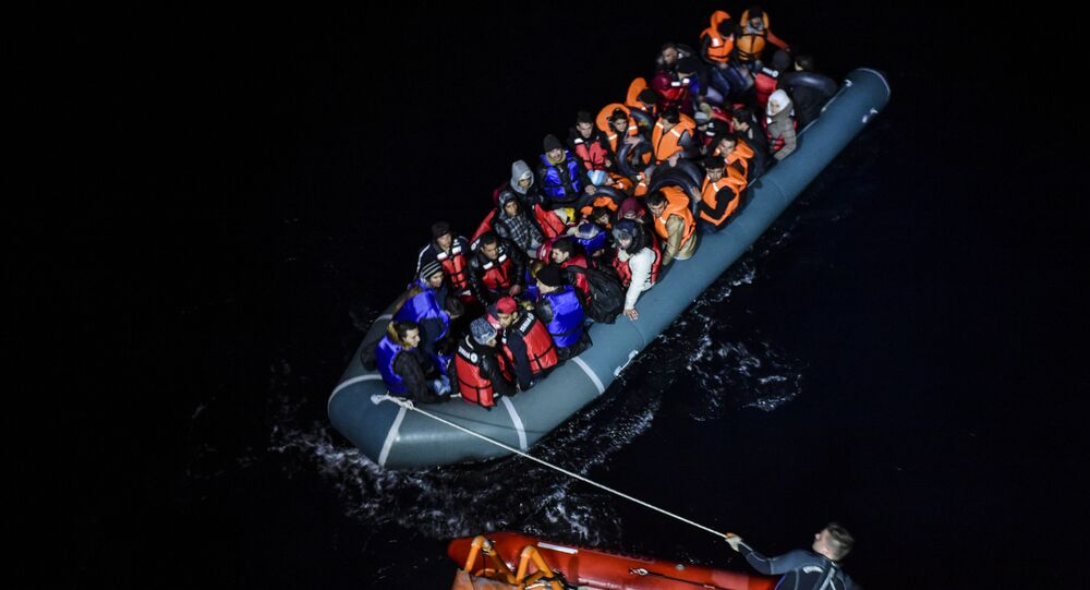 File photo of a member of the Turkish Coast Guard pulls an inflatable dinghy transporting Syrian migrants attempting to reach the Greek island of Chios, in the Agean Sea near Izmir in the night of December 9 to December 10, 2015