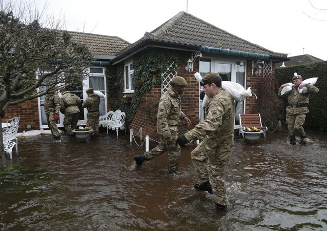 British army soldiers place sandbags at the entrance to a flooded house at Chertsey, England, Wednesday, Feb. 12, 2014