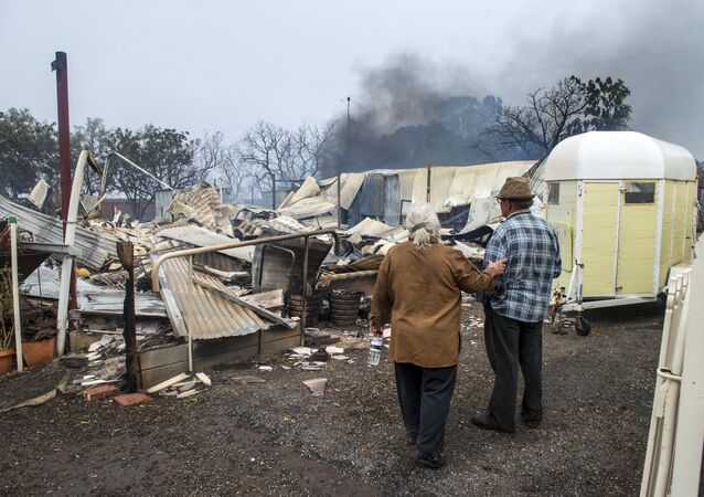 Property owners inspect their house that was destroyed by a bushfire near the town of Roseworthy, located north of Adelaide, South Australia, November 25, 2015
