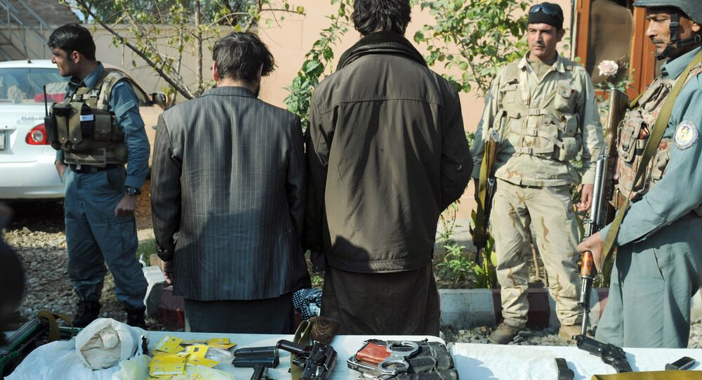 Afghan security forces stand guard around two arrested so-called IS fighters in Jalalabad, capital of Nangarhar province, Afghanistan, Wednesday, Dec. 23, 2015