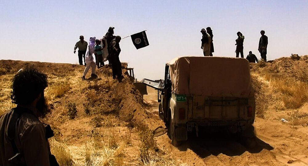 Suspected Daesh terrorists waving the trademark Jihadits flag as vehicles drive on a newly cut road through the Syrian-Iraqi border between the Iraqi Nineveh province and the Syrian town of Al-Hasakah. file photo