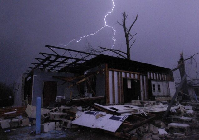 Lightning illuminates a house after a tornado touched down in Jefferson County, Ala., damaging several houses, Friday, Dec. 25, 2015, in Birmingham, Ala. A Christmastime wave of severe weather continued Friday.