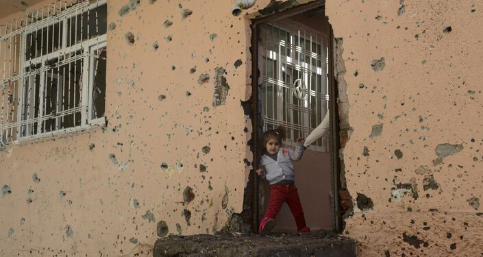 A girl stands at the entrance of a damaged house in the Sur district in Diyarbakir on December 11, 2015.