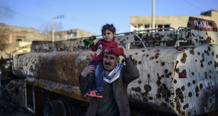 A man carries his daughter past a destroyed tanker truck in the southeastern city of Nusaybin, on December 24, 2015, in Mardin province.