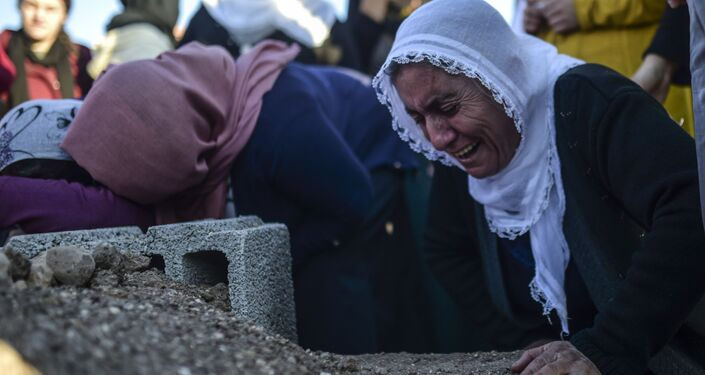 A relative grieves at the grave of Medeni Orak, killed  in the southeastern city of Nusaybin, on December 24, 2015, in Mardin province.