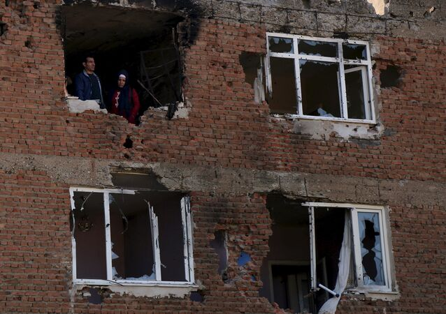 People look out from a building which was damaged during the security operations and clashes between Turkish security forces and Kurdish militants, in Sur district of Diyarbakir, Turkey, December 11, 2015.