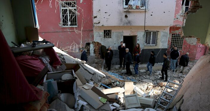 People look at buildings which were damaged during the security operations and clashes between Turkish security forces and Kurdish militants, in Sur district of Diyarbakir, Turkey, December 11, 2015.