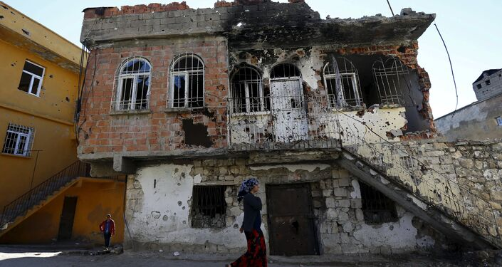 A woman walks past a building which was damaged during the security operations and clashes between Turkish security forces and Kurdish militants, in the southeastern town of Silvan in Diyarbakir province, Turkey, December 7, 2015.