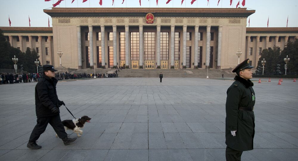 A Chinese paramilitary policeman, right, stands guard in front of the Great Hall of the People as a security officer walks past with a search dog before the opening session of the annual National People's Congress in Beijing, Thursday, March 5, 2015