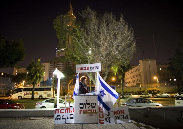 An Israeli activist hands out signs prior to a protest against an investigation into the funding of a number of left-wing NGO's in Israel