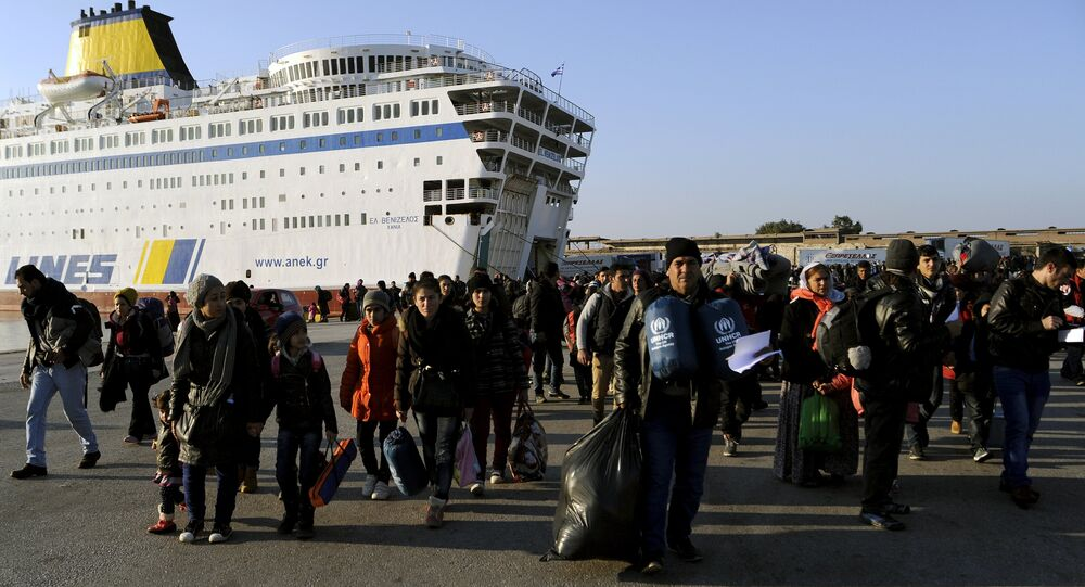Refugees and migrants walk after disembarking from the passenger ferry Eleftherios Venizelos from the island of Lesbos at the port of Piraeus, near Athens, Greece, December 26, 2015