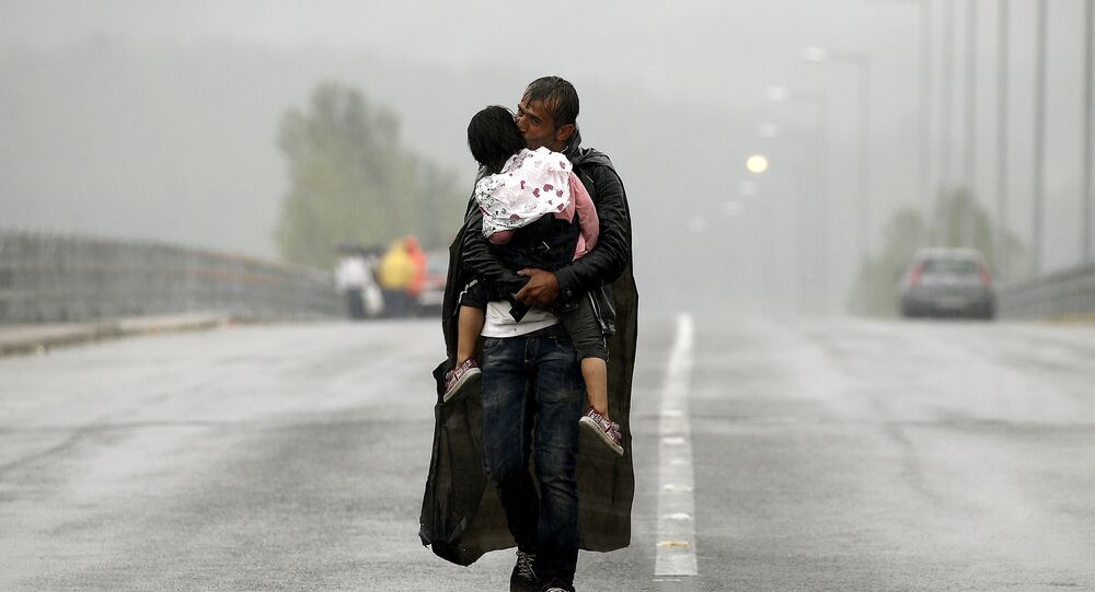 A Syrian refugee kisses his daughter as he walks through a rainstorm towards Greece's border with Macedonia, near the Greek village of Idomeni, September 10, 2015