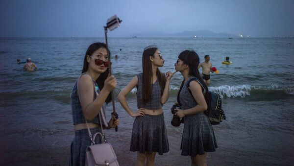Chinese women pose for a picture on the beach in Qingdao, eastern China's Shandong province on July 24, 2015 - Sputnik International