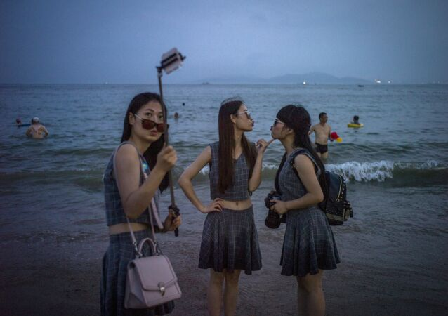 Chinese women pose for a picture on the beach in Qingdao, eastern China's Shandong province on July 24, 2015