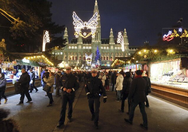 Two police officers patrol on the Viennese Christmas Market with the Viennese city hall in Vienna, Austria, Friday, Nov. 27, 2015.
