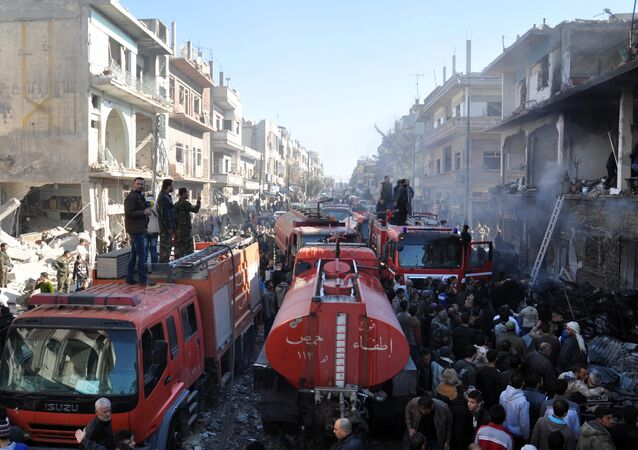 Syrians gather around fire-engines at the site of two car bomb attacks in the al-Zahraa neighbourhood of the central Syrian city of Homs on December 28, 2015.